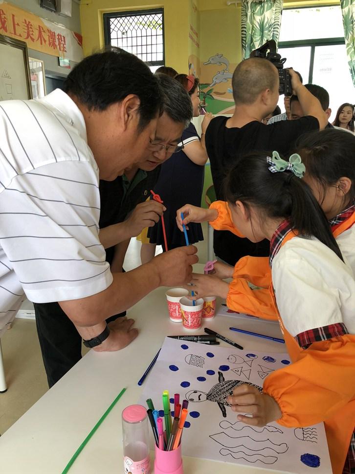 领导和学生一起完成美术作品